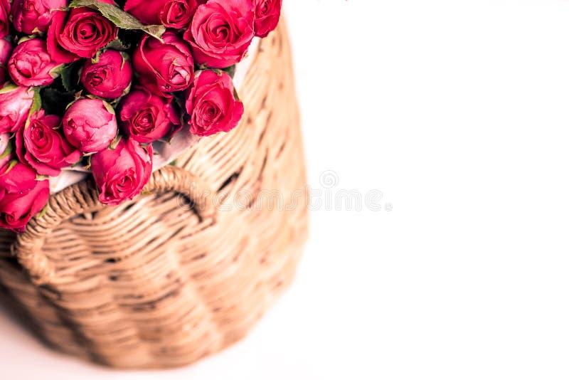Härlig bukett av röda rosor i korg som isoleras på vit royaltyfri bild