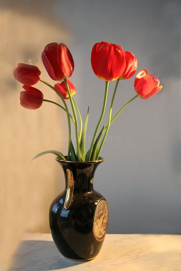 Härlig bukett av röda tulpan i en keramisk vas royaltyfri bild