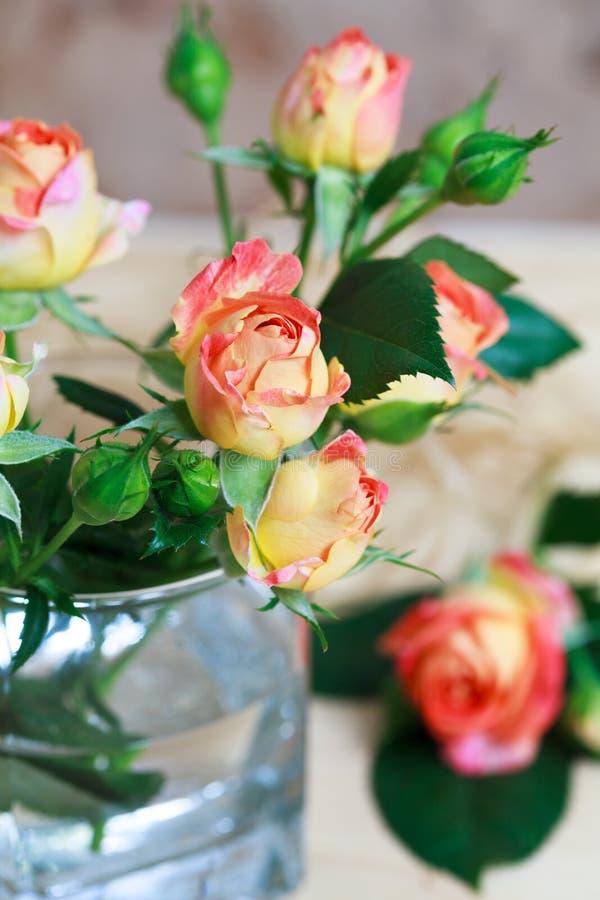 Härlig bukett av rosor i exponeringsglas på trätabell, selektivt f arkivfoton