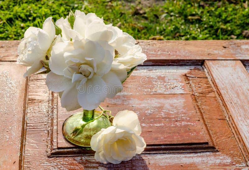 Härlig bukett av rosor med droppar i vas för grönt exponeringsglas på den gamla trätabellen royaltyfri bild