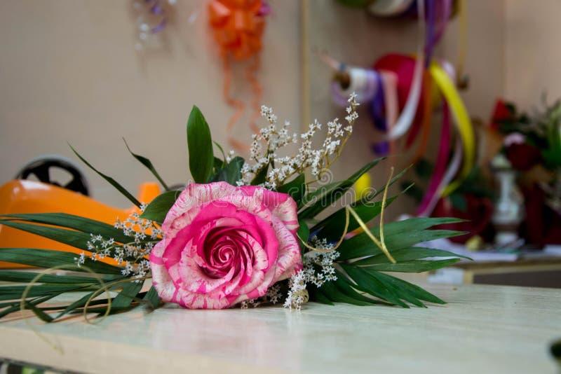 Härlig bukett, enkel röd ros på en trätabell i en blomsterhandel som blommar blomman för 8 marsch, moders dag, kvinnors dag royaltyfri fotografi