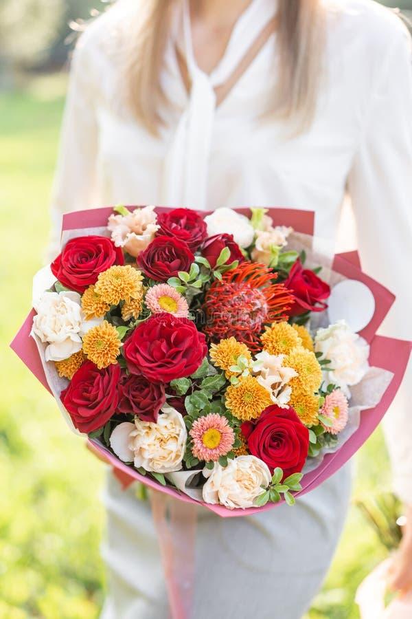 härlig bukett Ung flicka rymma blommaordningar med variation av färger Ljus gryning- eller solnedgångsol royaltyfria foton