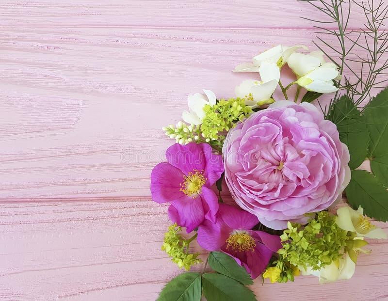 Härlig bukettram för rosor på en rosa träbakgrundsjasmin, magnolia royaltyfria bilder