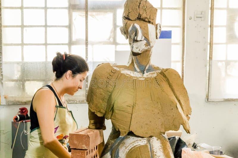 Härlig Caucasian konstnär som arbetar på hennes skulptur i en atelier royaltyfri bild