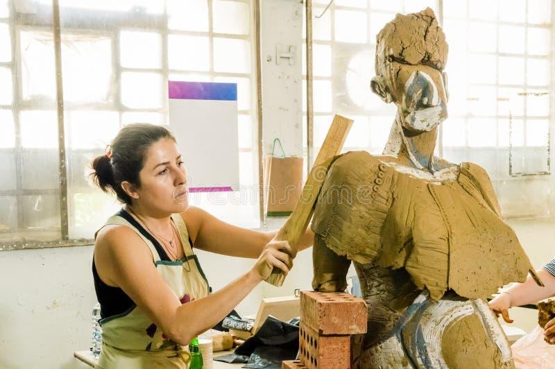 Härlig Caucasian konstnär som arbetar på hennes skulptur i en atelier fotografering för bildbyråer