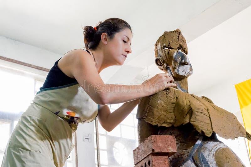 Härlig Caucasian konstnär som arbetar på hennes skulptur i en atelier royaltyfri foto