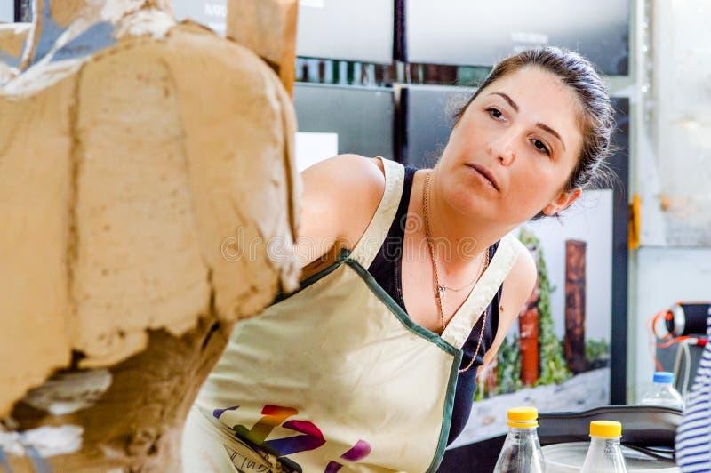 Härlig Caucasian konstnär som arbetar på hennes skulptur i en atelier royaltyfri fotografi