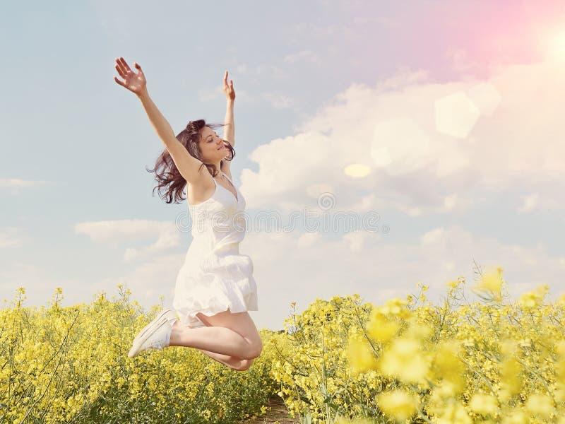 Härlig caucasian kvinna i den vita klänningen som hoppar upp med lyftt royaltyfria bilder