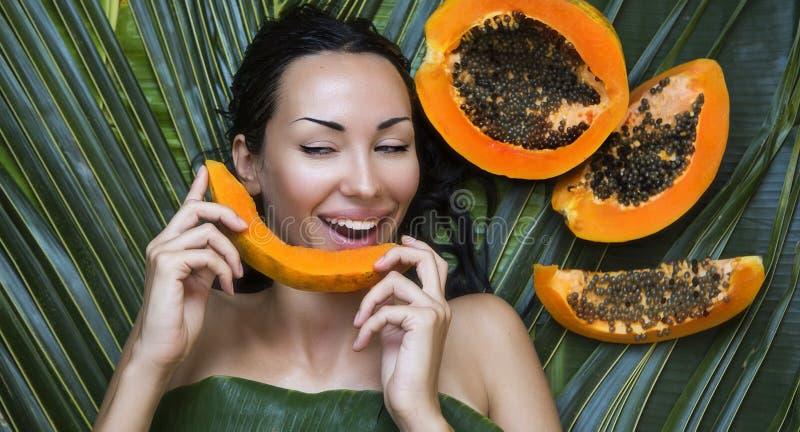 Härlig Caucasian kvinna med papayaen för ny frukt utomhus Honom royaltyfria foton