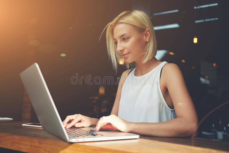 Härlig Caucasian kvinna som arbetar på netto-boken under morgonfrukosten i kaféstång royaltyfria foton