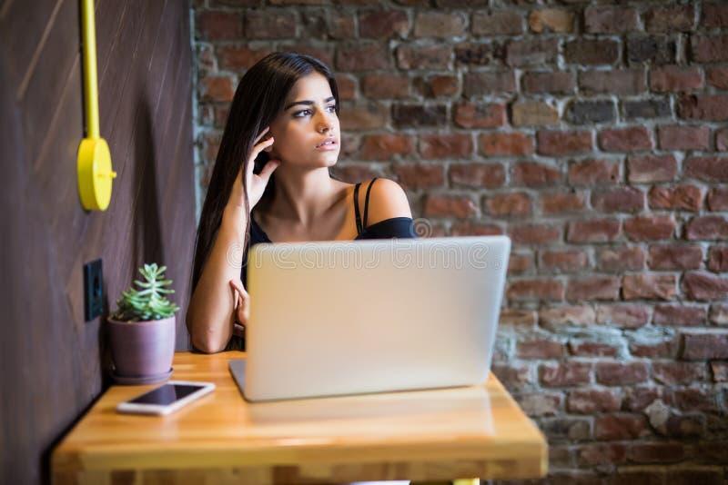Härlig Caucasian kvinna som drömmer om något, medan sitta med bärbar netbook i den moderna kaféstången, ung charmig kvinnlig f arkivbilder