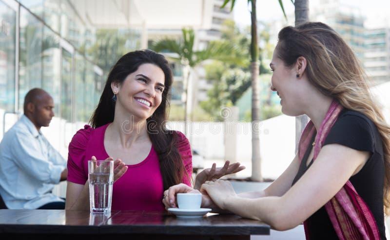 Härlig caucasian kvinna som två talar i en restaurang fotografering för bildbyråer