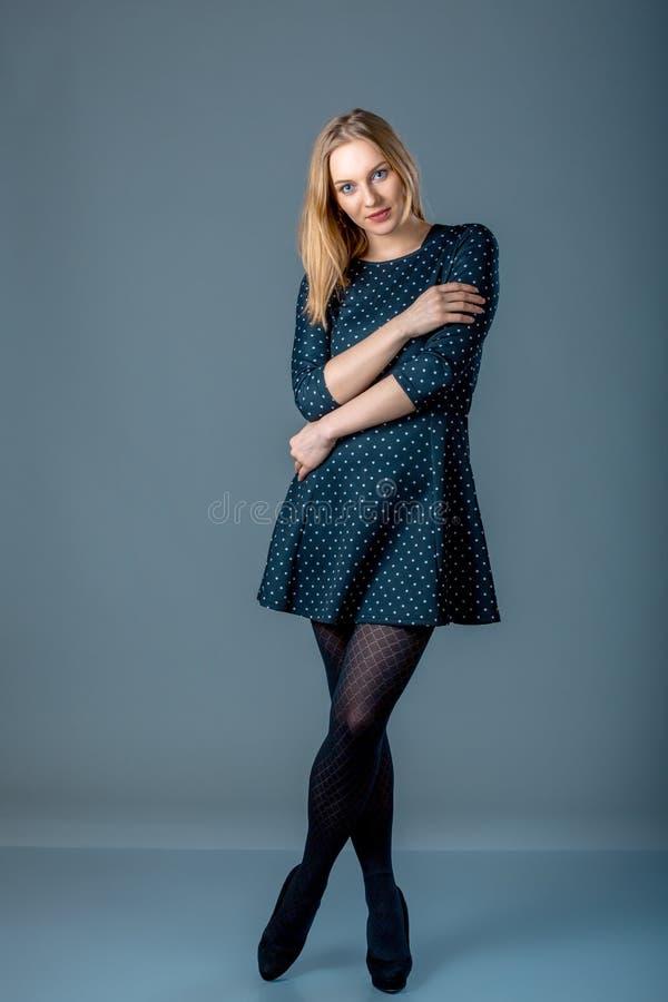 Härlig caucasian plus formatkvinnan i mörker - blå prickklänning Full längdstående av den attraktiva unga kvinnlign som poserar ö fotografering för bildbyråer