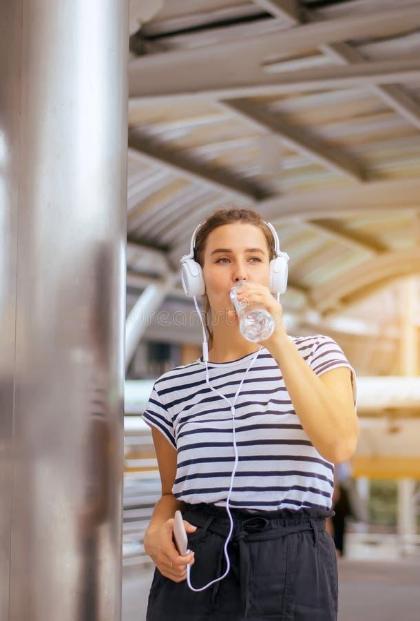 Härlig caucasian ung kvinna som använder headphonen som lyssnar till musik och dricksvatten på utomhus-, lyckligt och ler, positi arkivfoto
