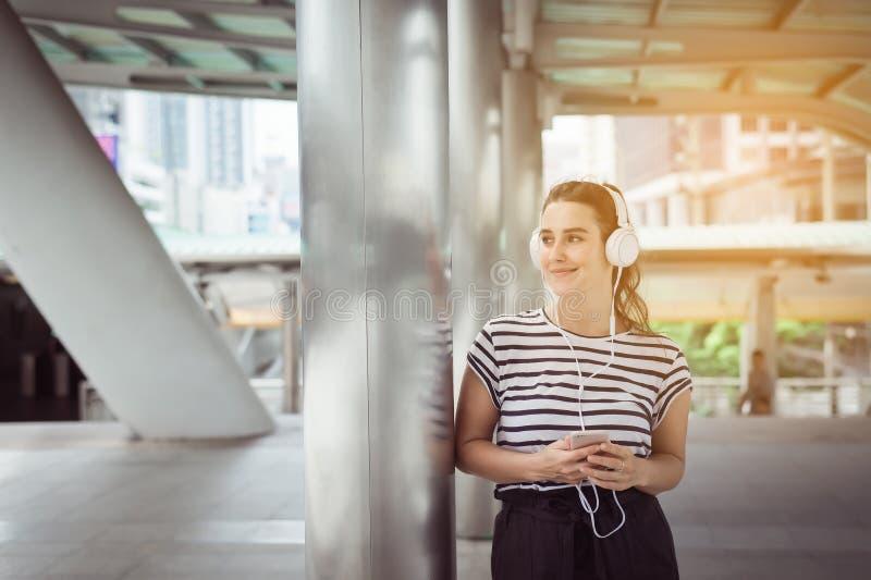 Härlig caucasian ung kvinna som använder headphonen och lyssnar till musik som är utomhus- som är lycklig och ler, tänka för real royaltyfri foto