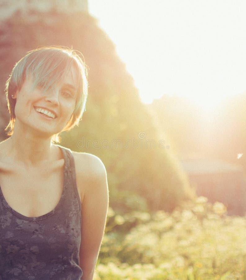 Härlig Caucasian ung kvinna som ser solnedgången med stenväggen bak henne Solnedgångfärger på henne framsida royaltyfri foto