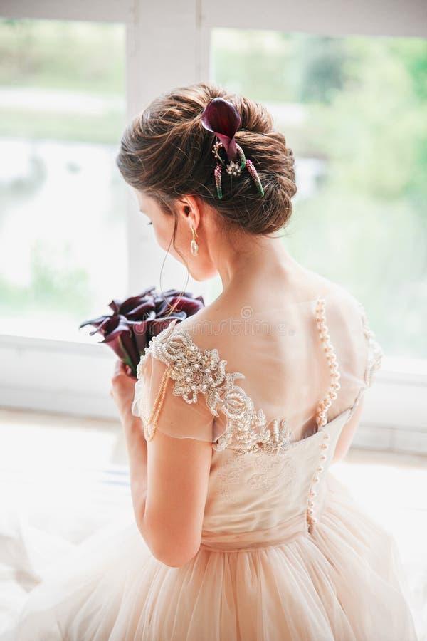 Härlig charmig brud i en lyxig klänning som ser upp Stående av lyckligt brudsammanträde i bröllopsklänning i en vit fotostudio royaltyfri foto