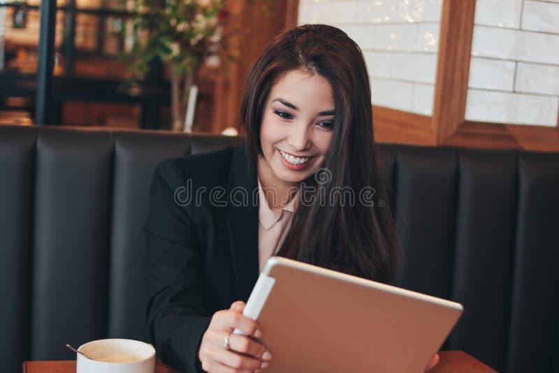 Härlig charmig brunett som ler den förvånade asiatiska flickan med minnestavlan på tabellen i kafé, student, freelancer eller ung royaltyfri foto
