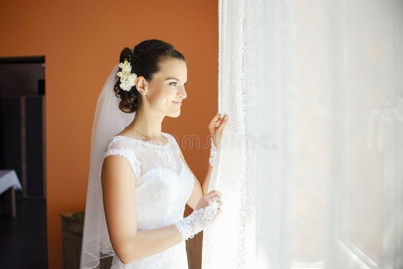 Härlig charmig ung brud som ut ser fönstret och le arkivbild