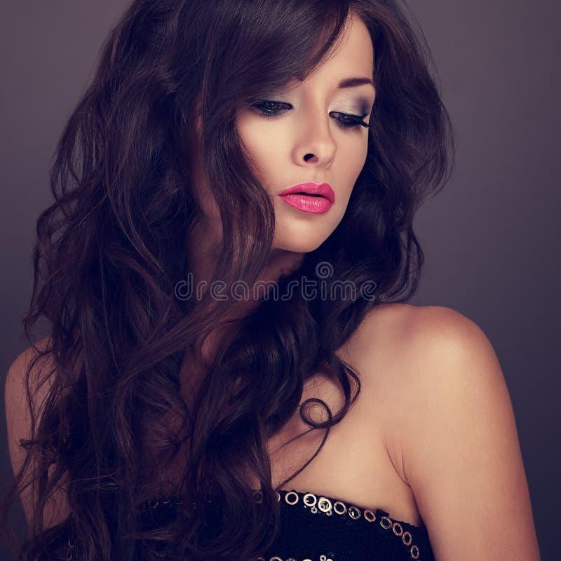 Härlig chic kvinnlig makeupmodell som poserar med lång lockig volym fotografering för bildbyråer