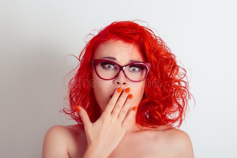 Härlig chockad förvånad kvinnaflicka med exponeringsglas som täcker munnen med handen royaltyfri bild