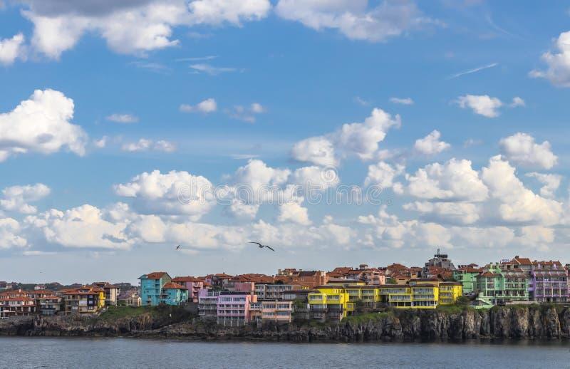 Härlig cityscape, färgrika hus vid havet, härligt ljus - blå himmel med fluffiga vita moln royaltyfria bilder