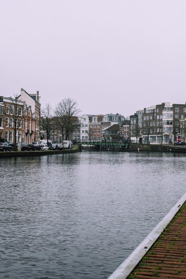 Härlig cityscape i Haarlem, Nederländerna Mycket små vågor på floden, bron och de mörka bricked husen på de båda sidorna arkivfoton