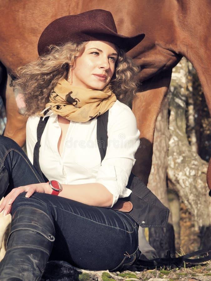 Härlig cowgirl med henne röd häst arkivbild