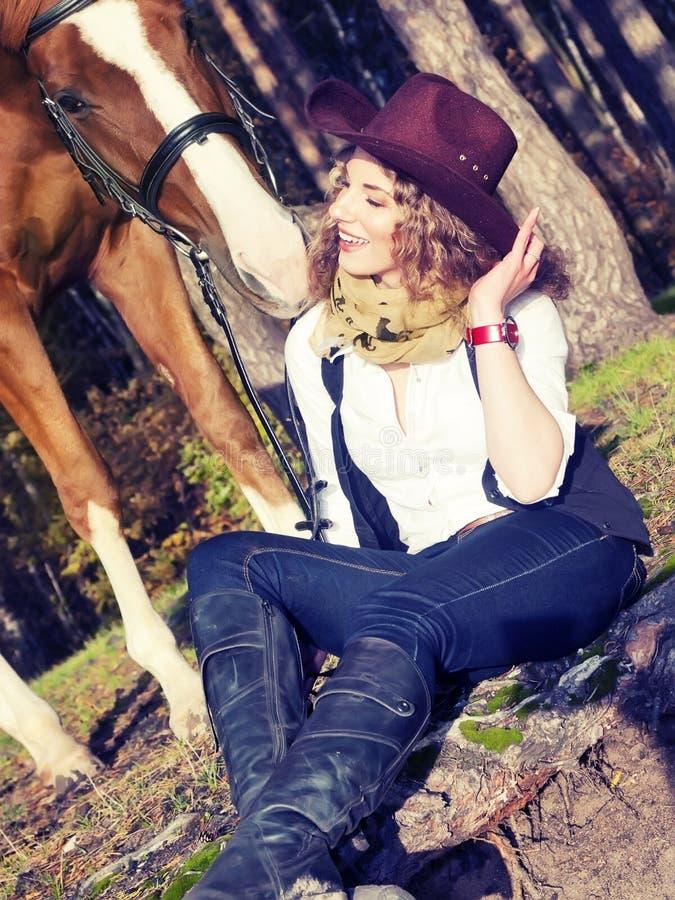 Härlig cowgirl med henne röd häst royaltyfri foto