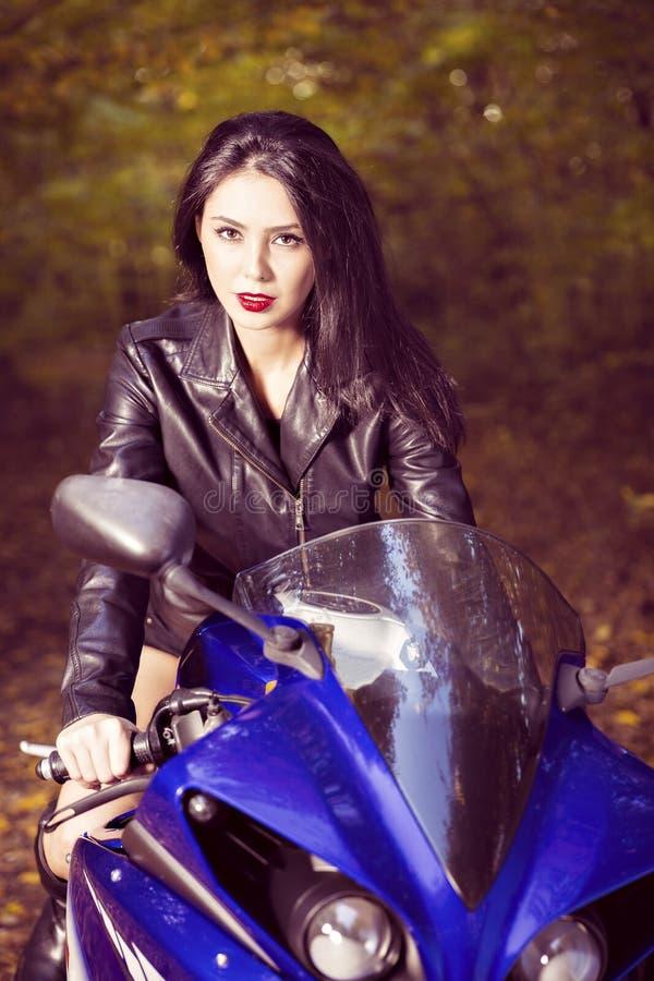 Härlig cyklistflicka på en motorcykel arkivbild