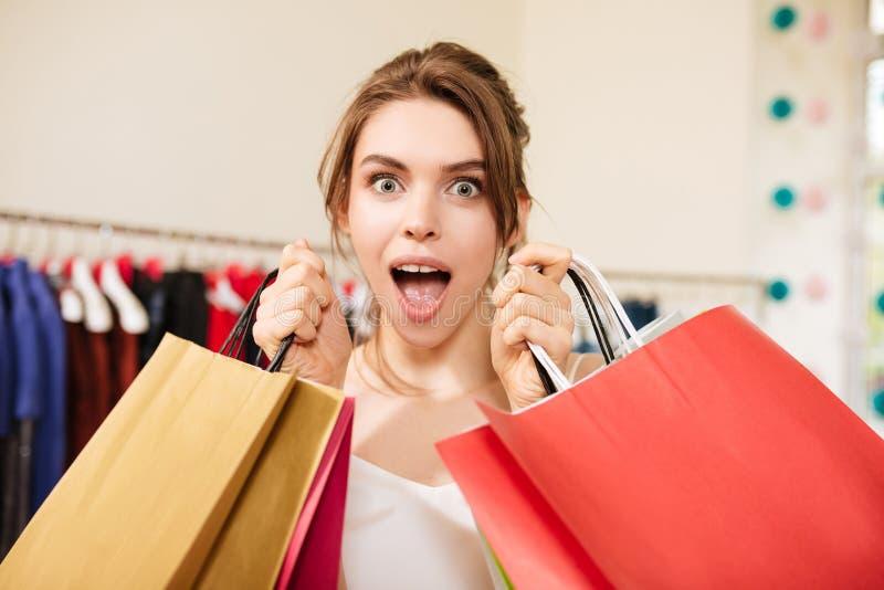 Härlig dam i den rosa byxdressen som står amazedly med shoppingpåsar i modeboutique royaltyfria foton