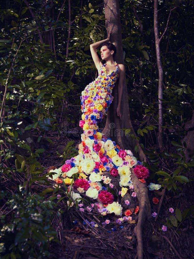 Härlig dam i klänning av blommor royaltyfri foto