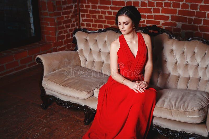 Härlig dam i röd klänning med ett aftonsmink fotografering för bildbyråer