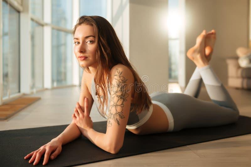 Härlig dam i sportig överkant och damasker som ligger på matt yoga och hänsynsfullt in camera ser royaltyfri foto