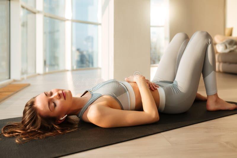 Härlig dam i sportig överkant och damasker som ligger på matt yoga stänga dreamily hennes ögon bredvid fönster royaltyfri bild