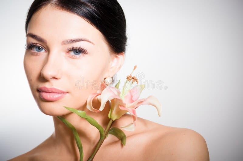 Härlig dam med lilly blomman perfekt hud arkivbild
