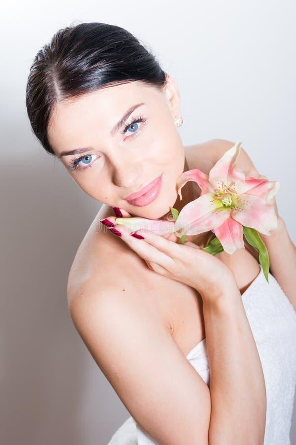 Härlig dam med lilly blomman perfekt hud arkivfoto