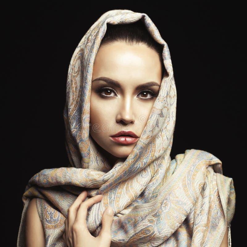 Härlig dam som slås in i en Orient sjal arkivbilder
