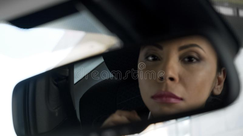 Härlig damreflexion i backspegel av bilen, misstänksam skuggig återförsäljare royaltyfri bild