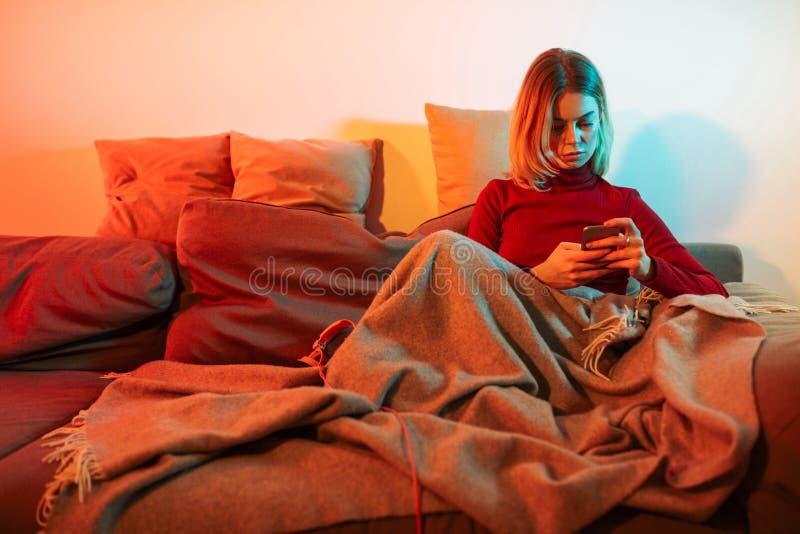 Härlig damsittig med plädet på soffan Ung kvinna som använder mobiltelefonen, medan spendera tid hemma arkivbilder