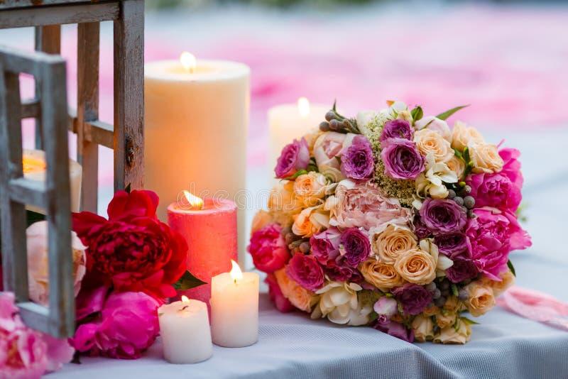 Härlig delikat brud- bukett bland garnering med stearinljus och nya blommor royaltyfri bild