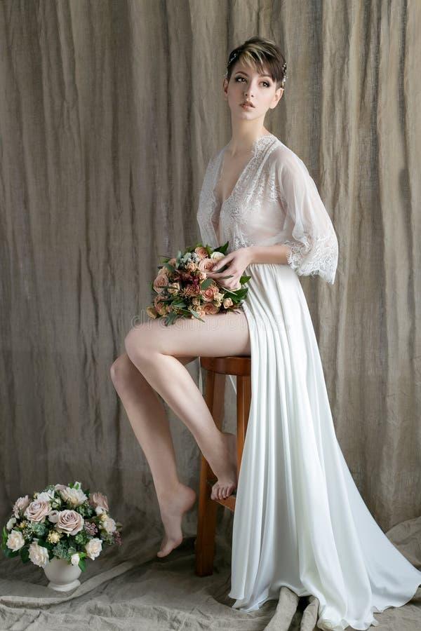 Härlig delikat brud för morgon med sexigt kort hår med ett siden- underklädersammanträde för liten krans på en stol med en bröllo arkivfoton