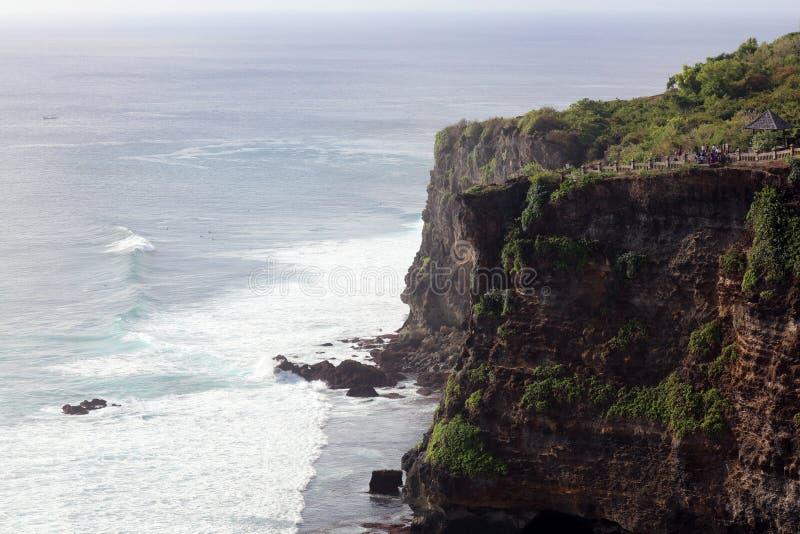 Härlig djungelstrandklippa med det blåa havet på Bali Indonesien med den gula sand- och gräsplanskogen i baksidan royaltyfri foto