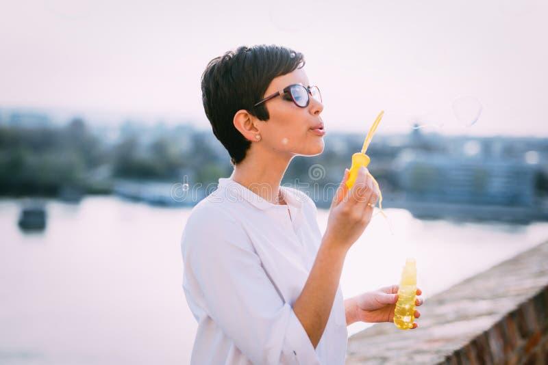 Härlig drömlik kvinna som blåser utomhus- såpbubblor royaltyfria bilder