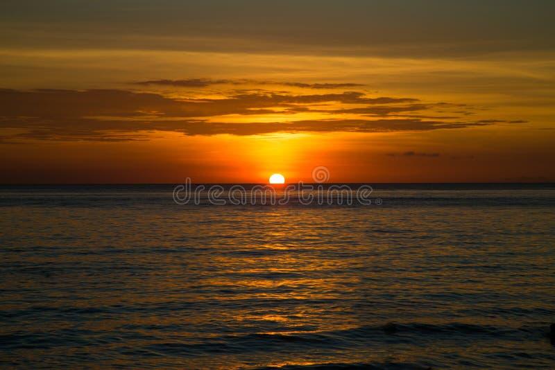 H?rlig dramatisk guld- himmel ?ver havet och reflexion p? solnedg?ngtid i sommaren arkivfoton