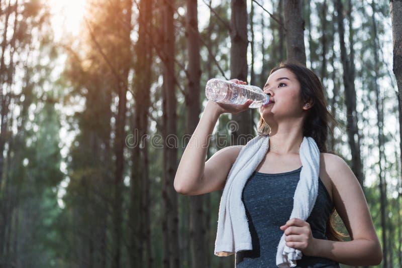 Härlig dricksvattenflaska för ung kvinna efter övningsfitne arkivfoton