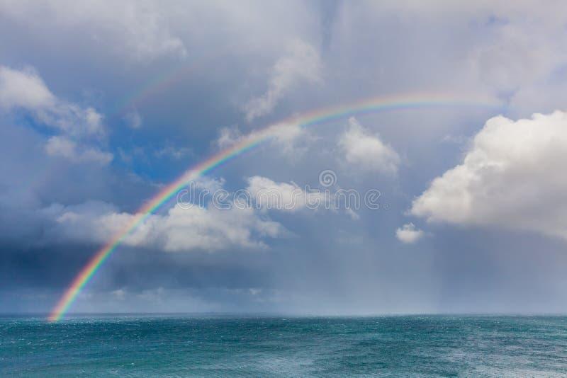 Härlig dubbel regnbåge över havvatten med stormmoln i himmelcloseupen arkivfoto