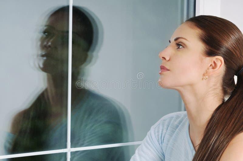 Härlig eftertänksam kvinna som hemma ser till och med fönstret arkivfoton