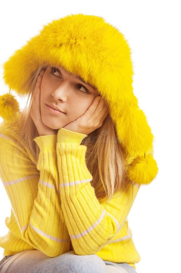 Härlig eftertänksam ung kvinna i gul pälshatt arkivbild