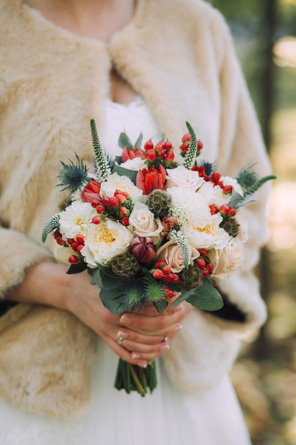 Härlig elegant höstbröllopbukett av vita rosor och röda blommor i händerna av bruden in i beige pälslag royaltyfria bilder